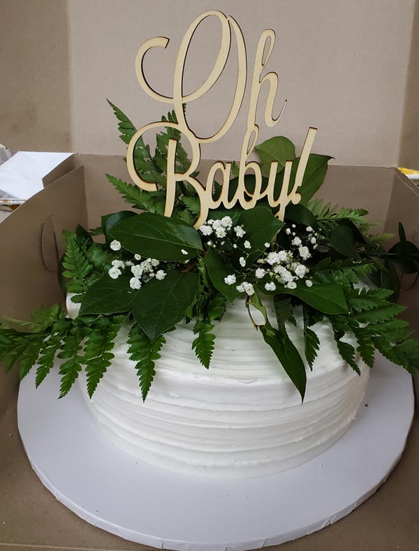 White cake with green decorating and words Oh Baby on top