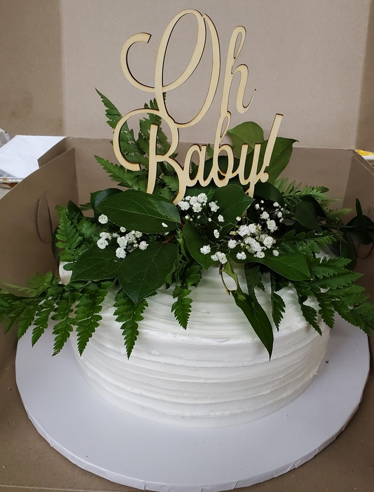 "Cake with greenery and ""Oh Baby"" on the top of it"