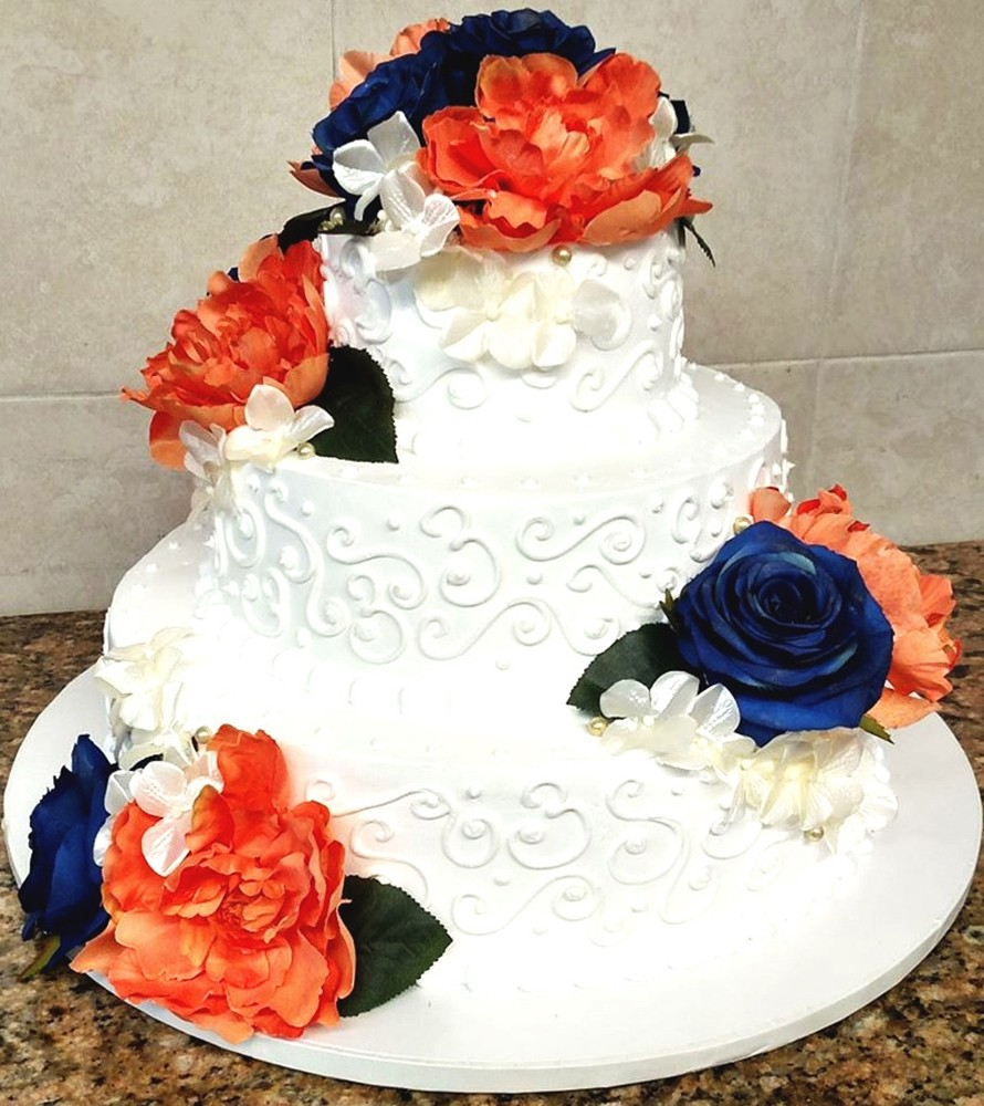 Tiered wedding cake with dark blue, orange and white flowers