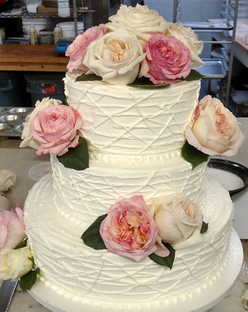 Tiered wedding cake with roses decorating it