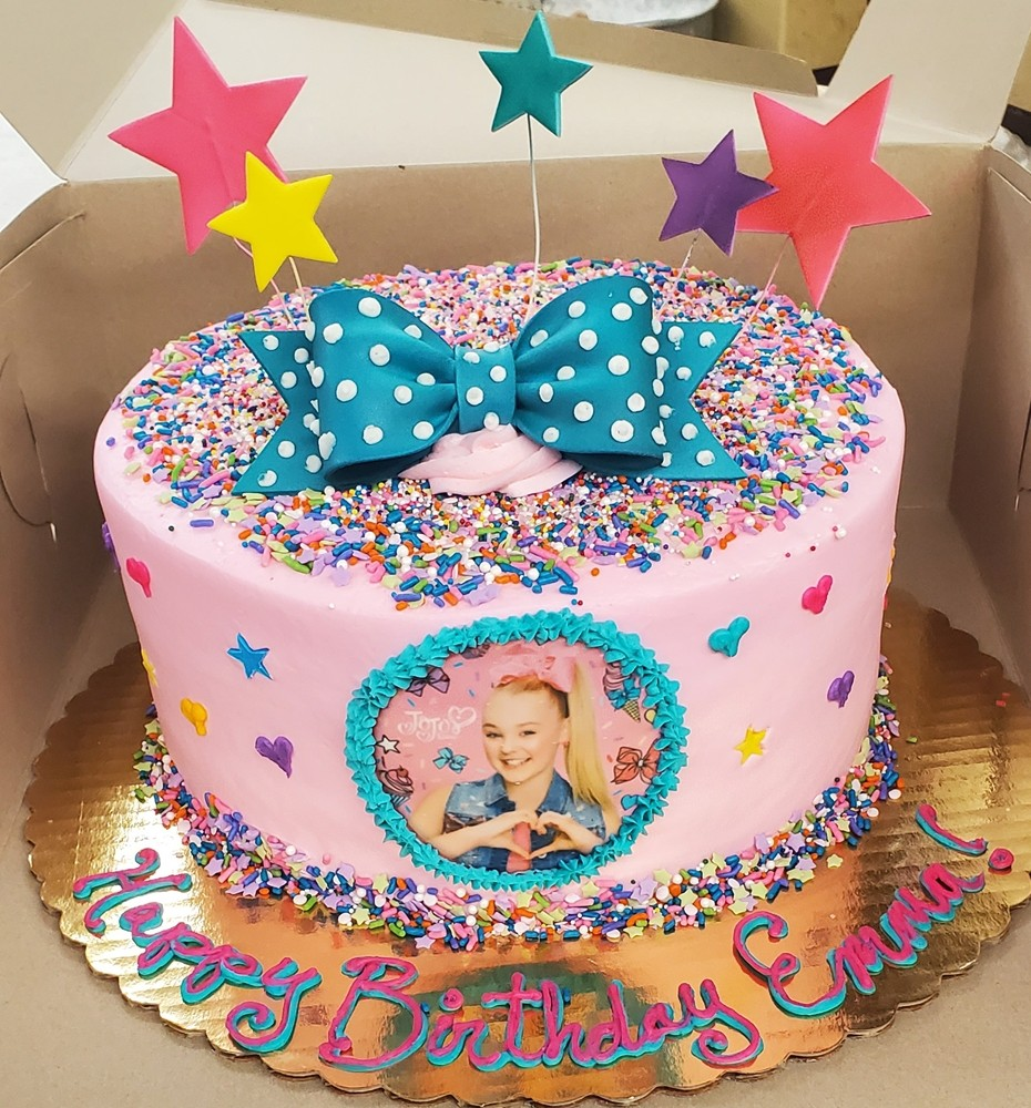 Pink birthday cake with blue polka dot ribbon and a pic of the birthday girl on the front
