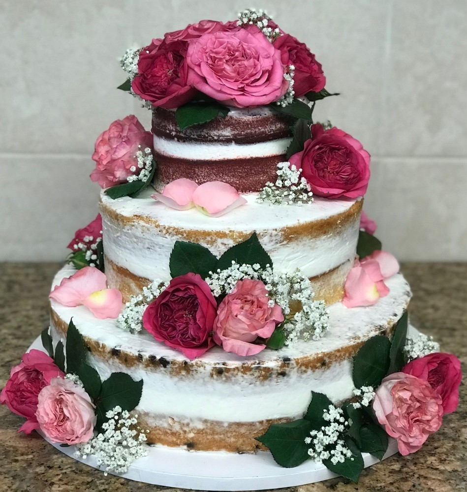 Tiered wedding cake with roses and babys breath decorating it