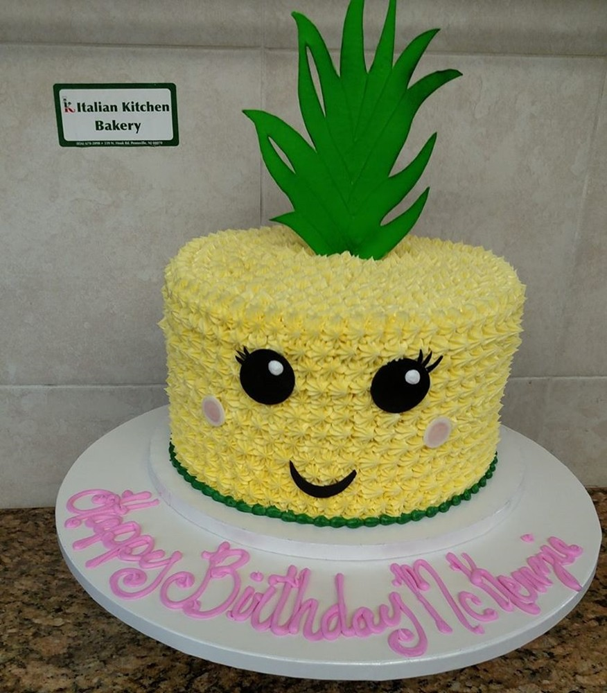 Birthday cake designed like a pineapple with a smiley face on it